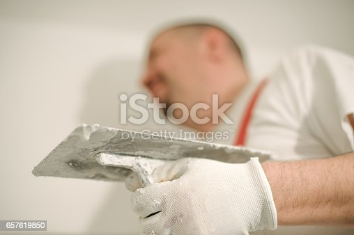 istock Construction worker plastering a wall with a spatula 657619850
