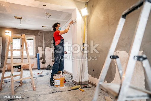 Construction worker plastering and smoothing concrete wall in room. Renovating apartment.