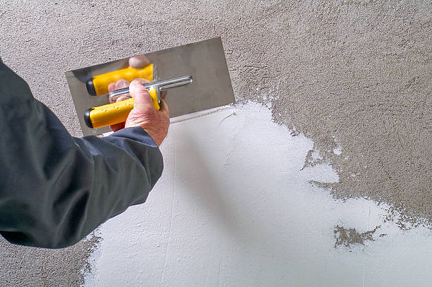Construction worker - plastering and smoothing concrete wall Construction worker - plastering and smoothing concrete wall with white cement by a steel trowel - spatula aligns plaster stock pictures, royalty-free photos & images