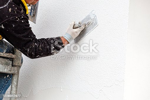 Applying silicone plaster to the wall of the house. Plastering wall.