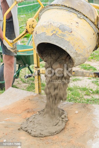 construction worker poors concrete out of  concrete mixer. process of creating cement on the construction site