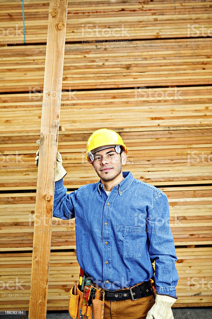 construction worker posing next to a piece of wood royalty-free stock photo