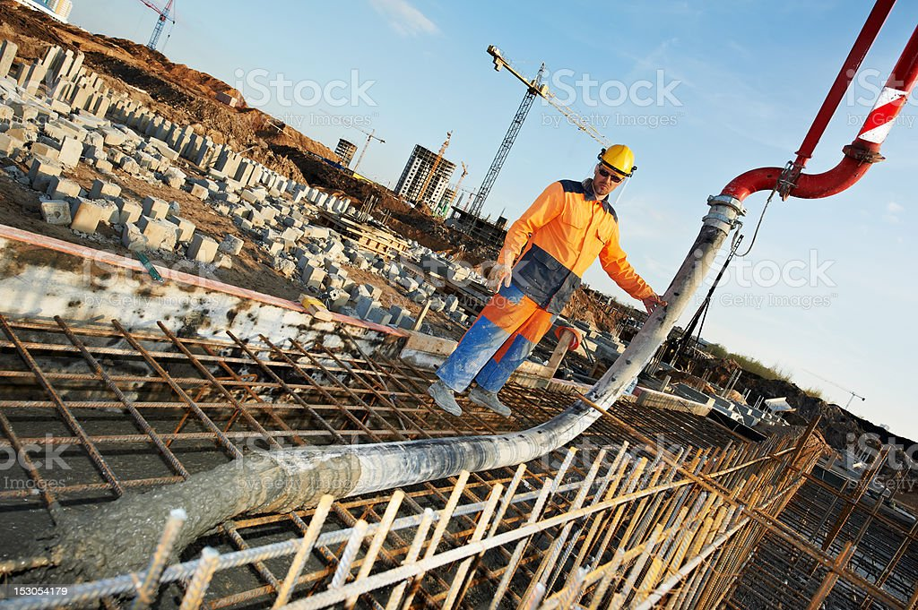 Construction worker pouring concrete on a job site  stock photo