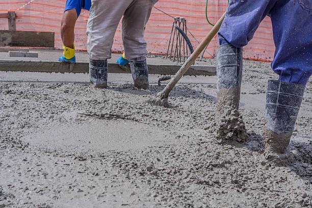 bauarbeiter compacting liquid zement in verstärkung für concreting etagen - betonwerkstein stock-fotos und bilder