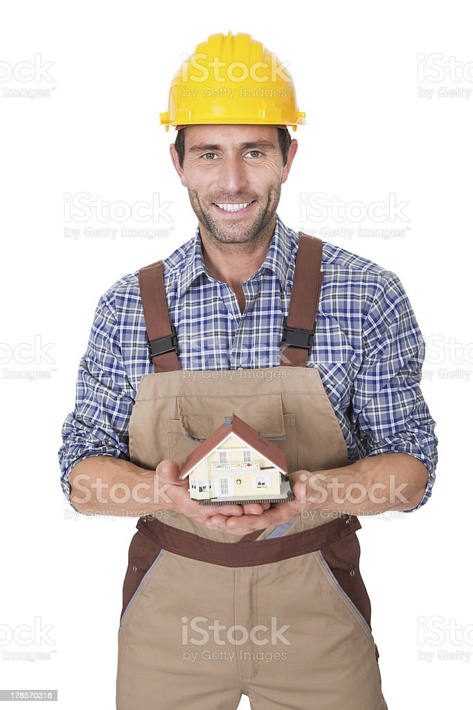 Construction worker presenting house model royalty-free stock photo