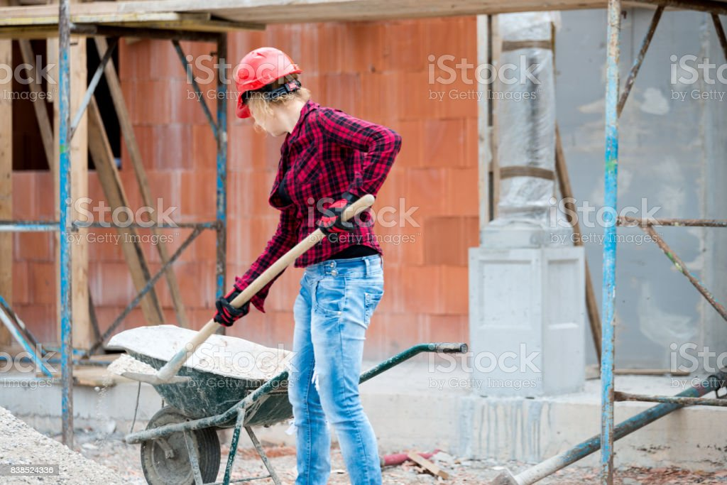 A construction worker puts sand in a wheelbarrow stock photo