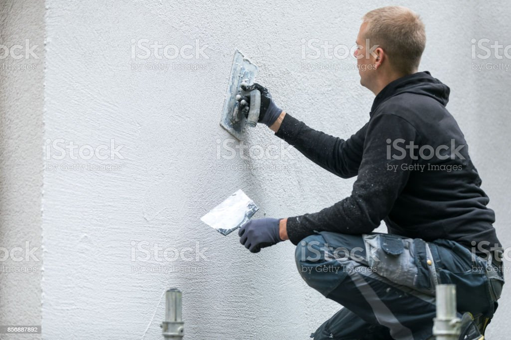 construction worker putting decorative plaster on house exterior stock photo