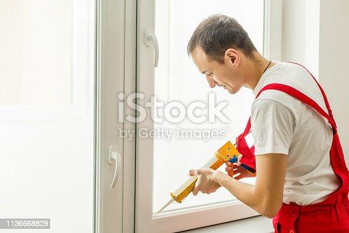 istock Construction worker putting sealing foam tape on window in house 1136668829