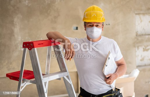 Portrait of a Latin American construction worker remodeling a house and wearing a facemask to avoid an infectious disease - reopening of businesses