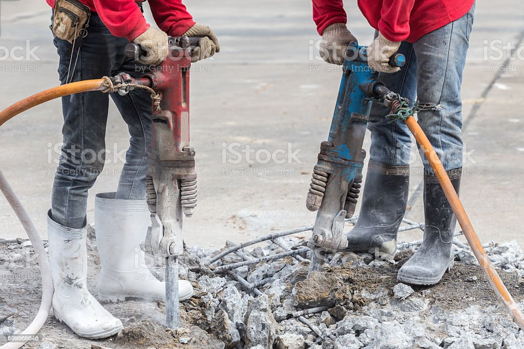 Construction worker removes excess concrete with drilling machin stock photo