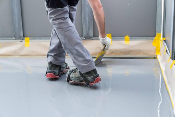Bauarbeiter renoviert Balkonboden und verteilt wasserdichtes Harz und Kleber vor dem Absplittern und Abdichten – Foto
