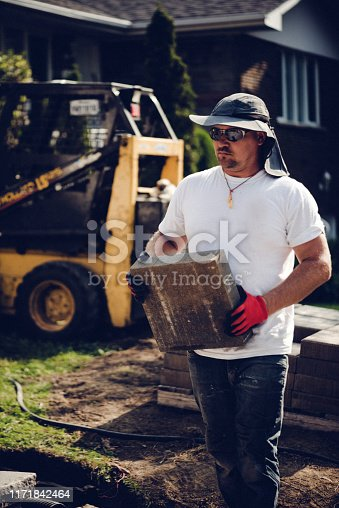 Construction worker renovating the front yard of a private house
