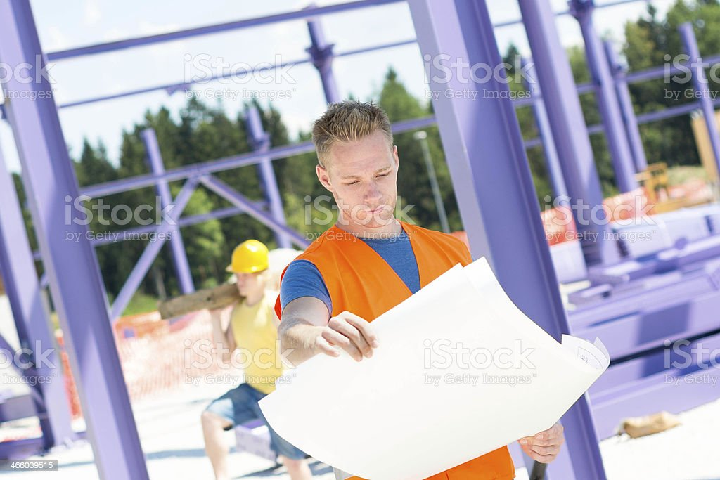 Construction worker  reviewing blueprint royalty-free stock photo
