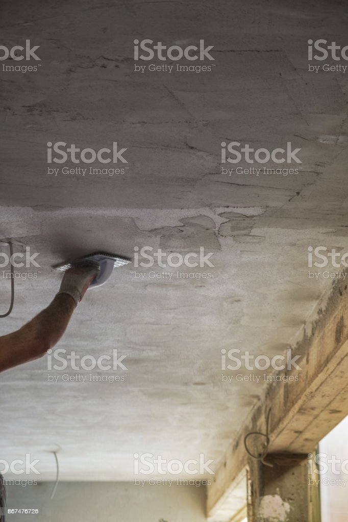 Construction worker scraping the cement plaster stock photo