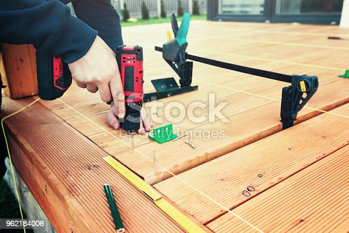 Construction worker screwing down wood deck with battery power screw gun or drill. The man screwed the terrace boards. Carpenter builds a terrace