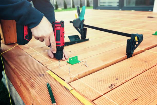 Bauarbeiter Holzdeck mit Batterie macht schraubengewehr oder Bohrmaschine festschrauben. – Foto