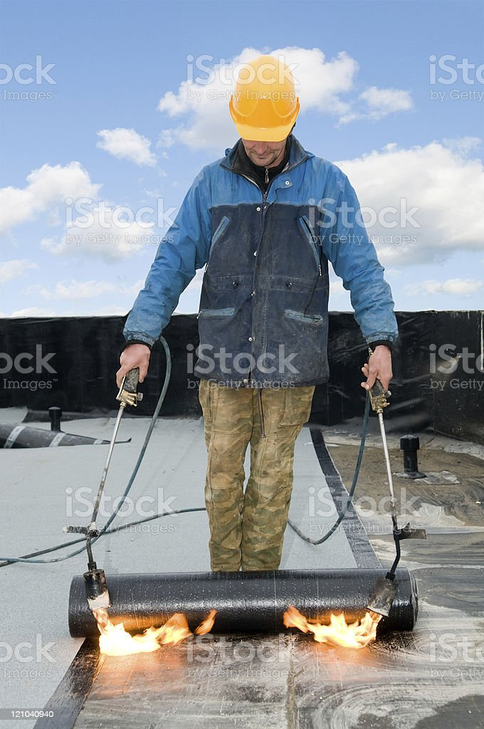 A construction worker sealing a roof covering with felt stock photo