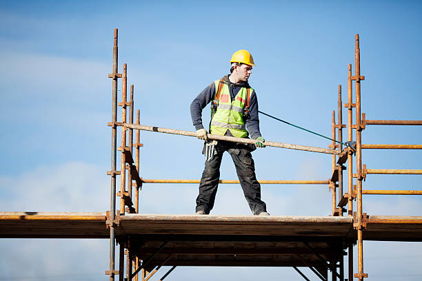 Construction worker setting up scaffolding against the sky Construction worker setting up scaffolding. scaffolding stock pictures, royalty-free photos & images