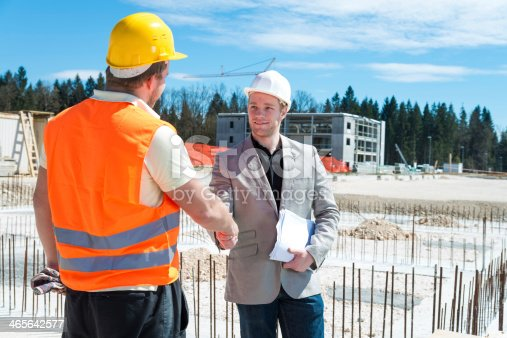 1071990712 istock photo Construction worker shaking hands with architect in a suit 465642577