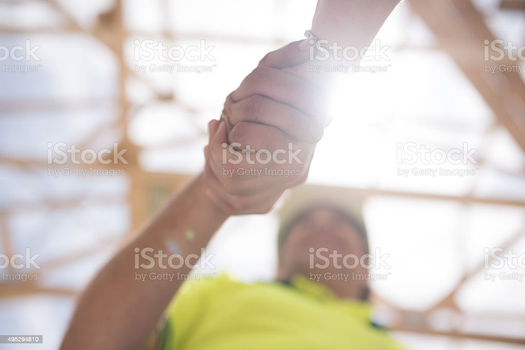 Construction worker shaking hands with manager stock photo