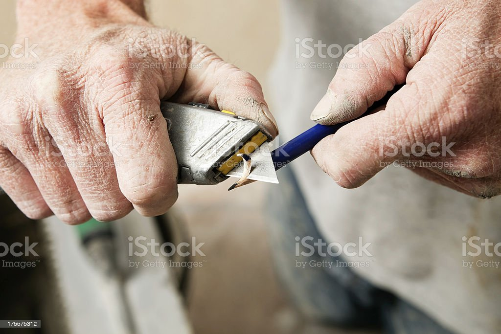 Construction Worker Sharpening Pencil with Utility Knife stock photo
