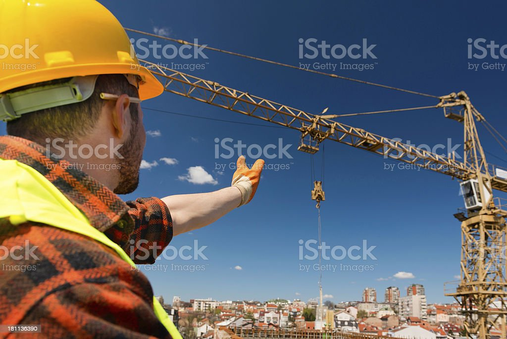 Construction worker signaling to crane operator stock photo