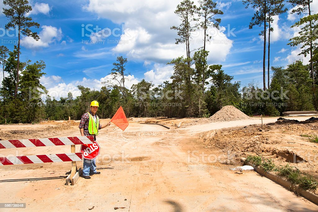 Construction worker, signalman directs traffic at job site. stock photo