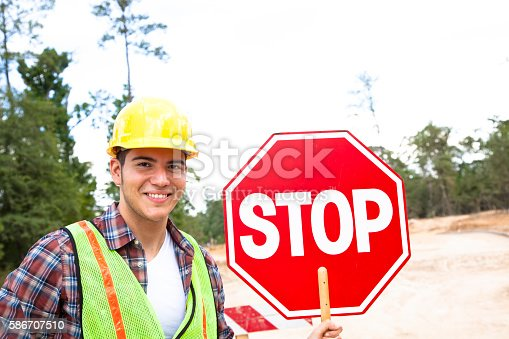 A Latin descent construction worker holds a stop sign to help direct traffic through a construction zone.  Cleared road with barricades in background of newly cleared land site for housing development.  He is wearing a hard hat and safety vest.