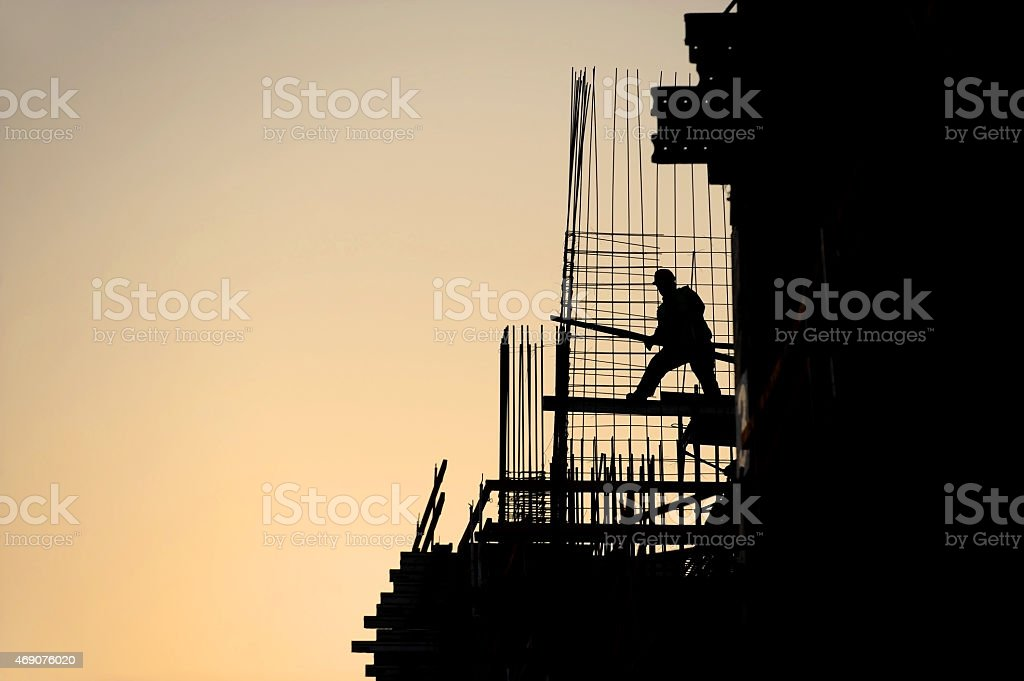 Construction worker silhouette at sunset stock photo