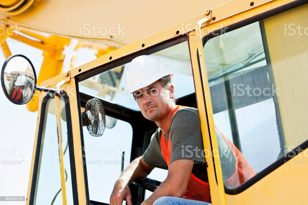 Construction worker sitting in crane stock photo