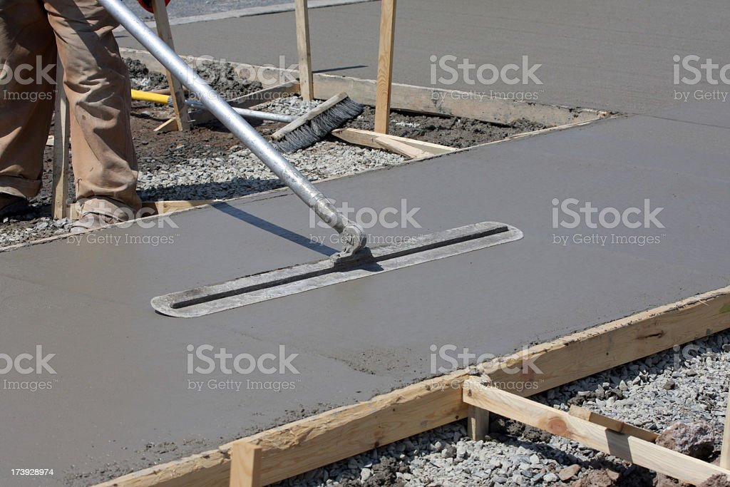 Construction worker smoothing out concrete on work site royalty-free stock photo