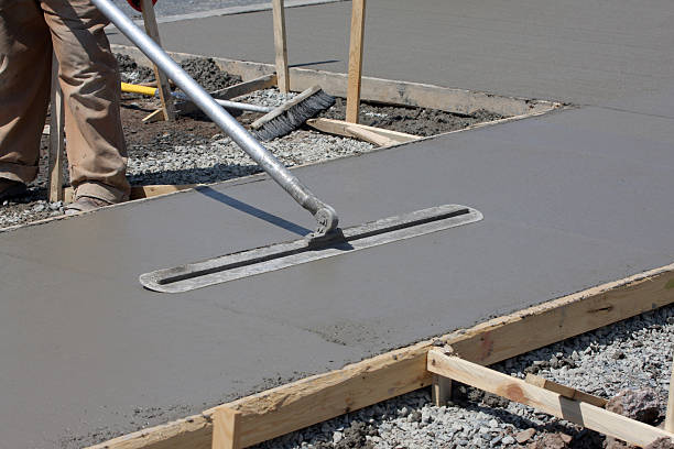 Construction worker smoothing out concrete on work site stock photo