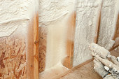 istock Construction Worker Spraying Expandable Foam Insulation between Wall Studs 185211977