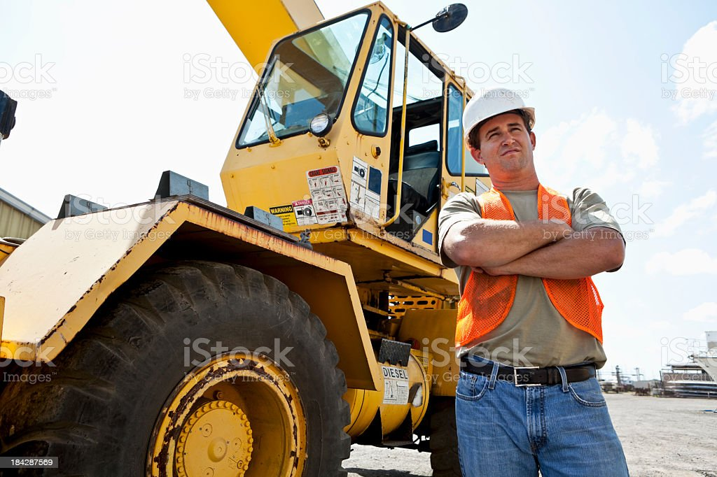 Construction worker standing in front of a crane stock photo