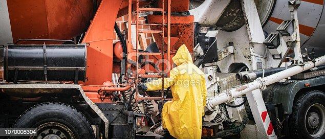 istock Construction worker standing near cement mixer 1070008304