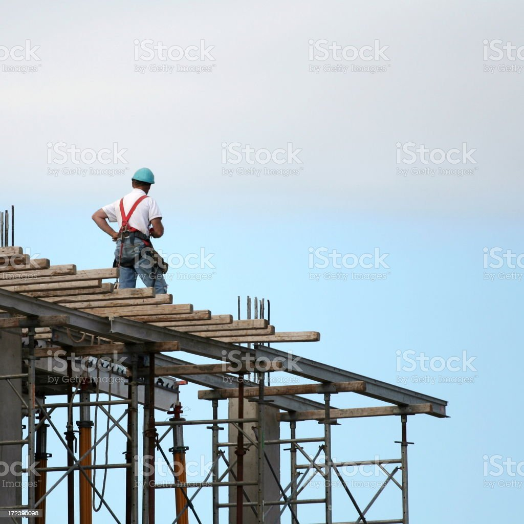 Construction worker standing on top of worksite royalty-free stock photo
