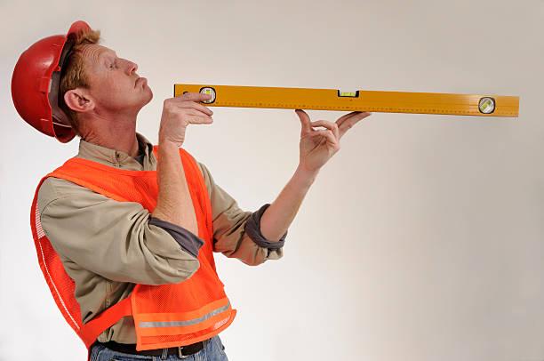 Construction worker stares down spirit level stock photo