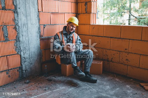 Young Inexperienced Building Worker Suffers from Knee Injury at the Construction Site. He has a Serious Injury at the Work