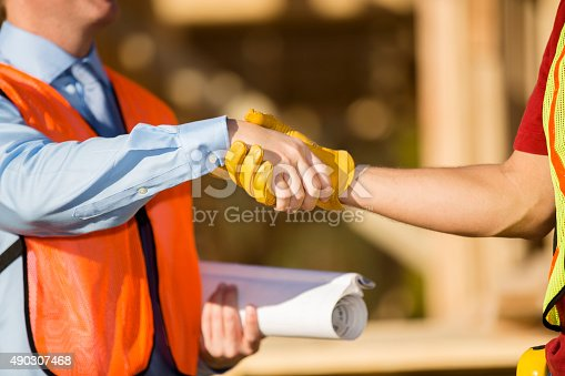 1071990712 istock photo Construction worker, supervisor discuss job at work site. Building. Handshake. 490307468