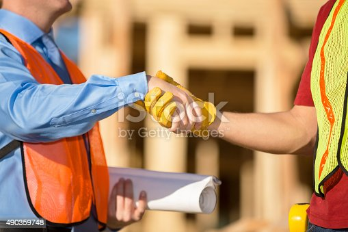 1071990712 istock photo Construction worker, supervisor discuss job at work site. Building. Handshake. 490359748