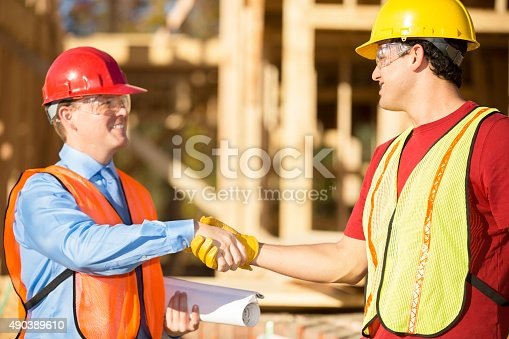 521012560istockphoto Construction worker, supervisor discuss job at work site. Building. Handshake. 490389610