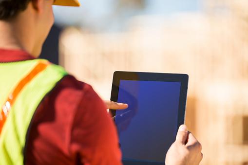 Construction worker, supervisor inspects work at building site. Digital tablet.