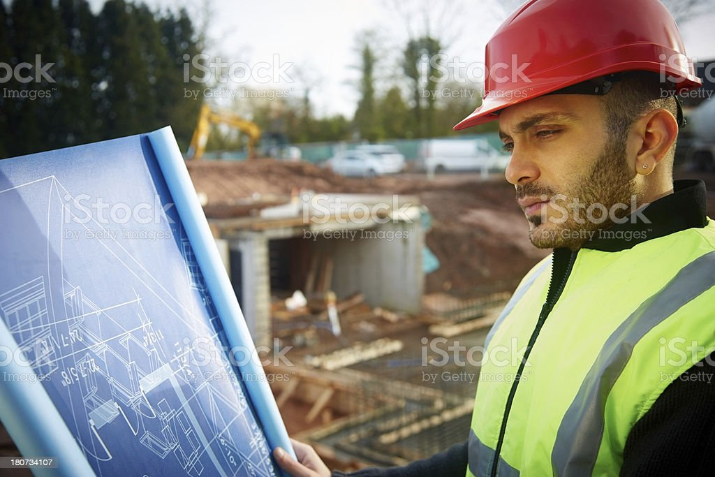 Construction worker surveying plans at site royalty-free stock photo