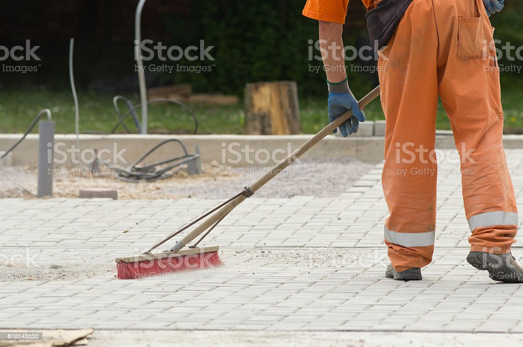Construction worker sweeping - Photo