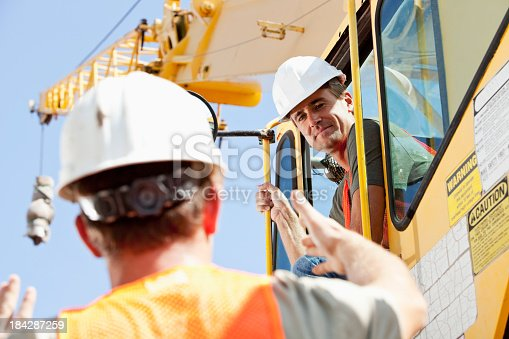 Low angle view of two construction workers operating a crane.  The driver is looking down at a man on the ground who is talking to him, giving directions and gesturing with his hands.  They are both wearing white hard hats and orange safety vests.  The focus is on the man in the cab of the construction equipment and we see the back of the head of the other man who is maybe the foreman.