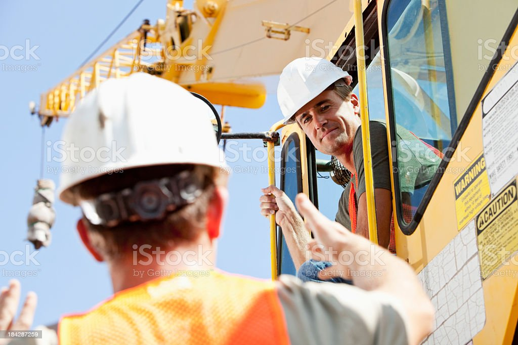 Construction worker talking to crane operator stock photo
