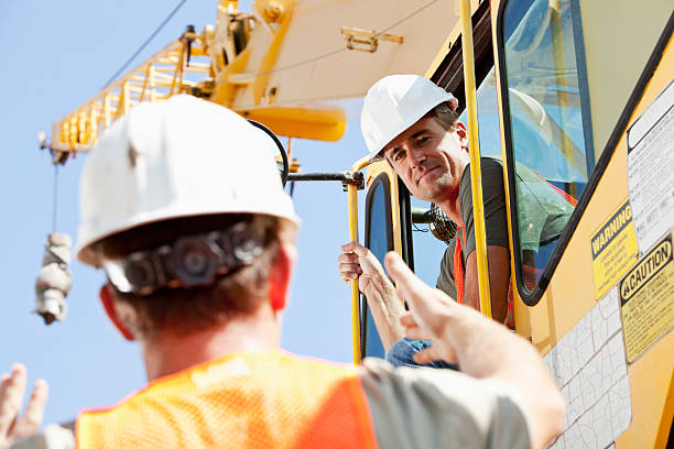 construction worker talking to crane operator - crane construction machinery stock pictures, royalty-free photos & images