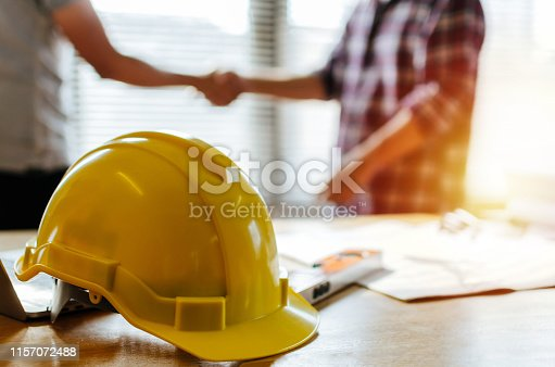 1055059750 istock photo construction worker team hands shaking greeting start up plan new project contract behind yellow safety helmet on workplace desk in office center at construction site, partnership, contractor concept 1157072488