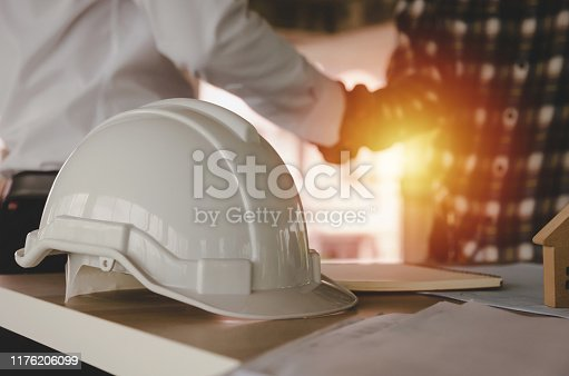 1055059750istockphoto construction worker team hands shaking greeting start up plan new project contract behind white safety helmet on workplace desk in office center at construction site, partnership, contractor concept 1176206099