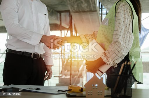 construction worker team handshake after consultation meeting to greeting start up plan new project contract in office center at construction site, teamwork, partnership and contractor concept